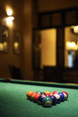 Pool balls on billiards table in cozy bar — Stock fotografie