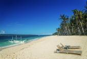 Lounge chairs and traditional boat on puka beach in boracay phil — Stock Photo