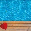 Swimming pool with blue clear water, wooden deck and red paper h — Stock Photo #64363523