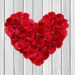 Heart from red rose petals on wooden table — Stock Photo #64437847