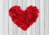 Heart from red rose petals on wooden table — Stock Photo