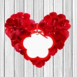 Heart from red rose petals and tag on wooden table — Stock Photo #66837177