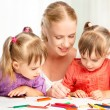 Children twin sisters draw paints with her mother in kindergarten — Stock Photo #51880347