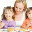 Children twin sisters draw paints with her mother in kindergarten on a white background — Stock Photo #52721521