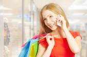 Happy woman with  bags on shopping, talking on phone — Stockfoto