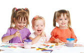 Happy little girl in kindergarten draw paints on white background — Foto Stock