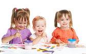 Happy little girl in kindergarten draw paints on white background — Photo