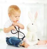 Juegos de bebé en doctor conejito de juguete y un estetoscopio — Foto de Stock