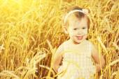 Happy little girl in a field of golden wheat in the summer — Stock Photo