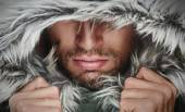 Brutal face of a man with beard bristles and hooded winter — Stock Photo