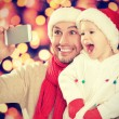 Selfe in Christmas. happy family dad playing with daughter and photographed on mobile phone — Stock Photo #53793831