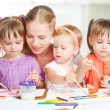 Children twin sisters draw paints with her mother in kindergarten — Stock Photo #53793919