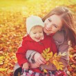 Happy family: mother and child little daughter play cuddling on autumn — Stock Photo