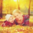 Happy family: mother and child little daughter playing and laughing in autumn — Stock Photo #54221833
