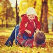 Happy family: mother and child little daughter playing and laughing in autumn — Stock Photo #54221845