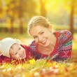 Happy family: mother and child little daughter playing and laughing in autumn — Stock Photo #54221847