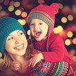 Happy family mother and little daughter playing in the winter for Christmas — Stock Photo #55504855