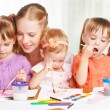 Children twin sisters draw paints with her mother in kindergarten — Stock Photo #56115633