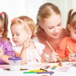 Children twin sisters draw paints with her mother in kindergarten — Stock Photo #56115649