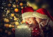 Christmas magic gift box and a happy family mother and daughter baby girl — Stock Photo