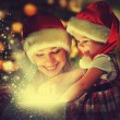 Christmas magic gift box and a happy family mother and daughter baby girl — Foto Stock #56453671