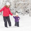 Happy family mother and baby girl daughter run, walk and playing in winter snow — Stock Photo #58692161