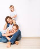 Happy family on  floor near  empty  wall in the apartment bought on mortgage — Stock Photo