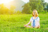 Young woman doing yoga on green grass — Stock Photo