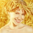 Beautiful happy girl in wreath in wheat field in summer — Stock Photo #64996991