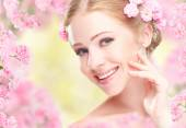 Beauty face of young happy beautiful woman with pink flowers in  — Стоковое фото
