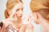 Young beautiful woman apply makeup eyeshadow front of  mirror — Stock Photo