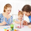 Happy family: mother, father and child  daughter draw paints — Stock Photo #67493525