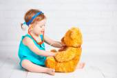 Girl playing doctor and treats teddy bear — Stock Photo