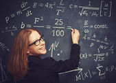 Happy girl student, the teacher writes on  blackboard chalk form — Stock Photo