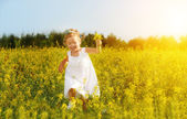 Happy little child girl running on field with yellow flowers — Stock Photo