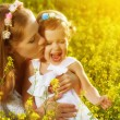 Happy family in summer meadow, mother kissing little daughter ch — Stock Photo #76419097