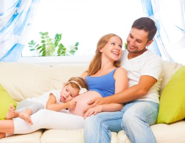 Happy family. pregnant mother, father, and child daughter at hom