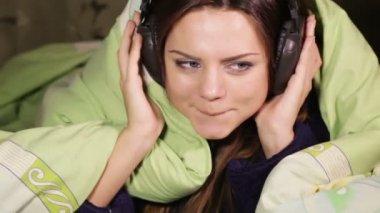 ヘッドフォン笑顔ベッド ホームを持つ少女 — ストックビデオ