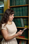 A woman with a gadget in the library — Stock Photo