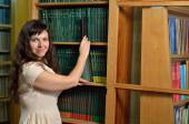 A woman with a gadget in the library — Stockfoto