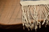 Edge of the wood table with a homespun towel — Stock Photo