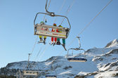 Skiers in the chair lift above the snow hill — Stock Photo