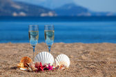 Wines glasses,shells,starfishes on a beach — Stock Photo