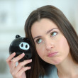 Woman putting coin into a piggy bank — Stock Photo #67272365