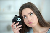 Woman putting coin into a piggy bank — Stock Photo