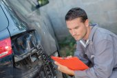 Mechanic inspecting damaged car — Stockfoto