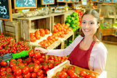 Shop worker carrying a crate of tomatoes — Stock Photo