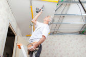 Builder putting up a suspended ceiling — Stock Photo