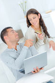 Playful couple arguing over on-line shopping — Stock Photo