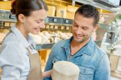 Giving advice in a cheese shop — Stock Photo